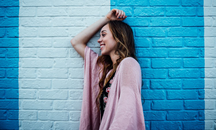 Brunette woman wearing a pink cardigan smiles as she leans sideways against a brick wall painted 2 colors of blue
