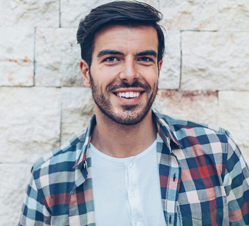 A man with a plaid shirt and veneers smiling in front of a brick wall