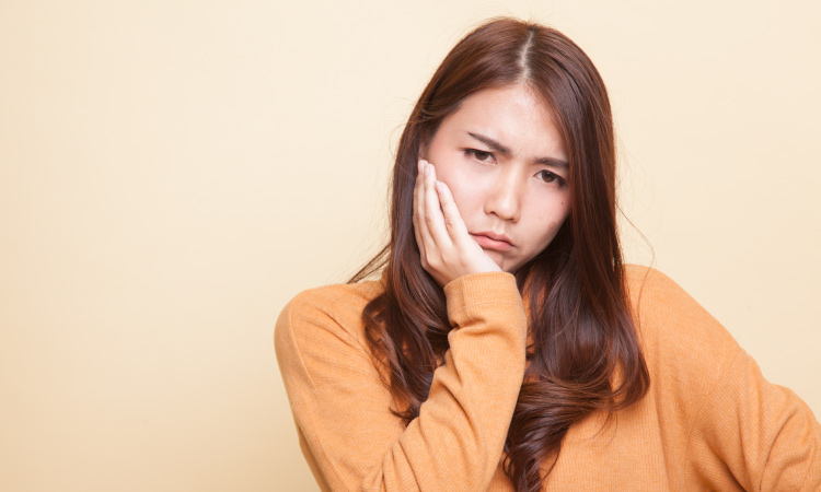 Brunette woman wearing a yellow sweater cringes and touches her jaw due to TMJ pain