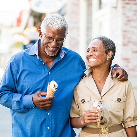 An older couple walking down the street with icecream cones