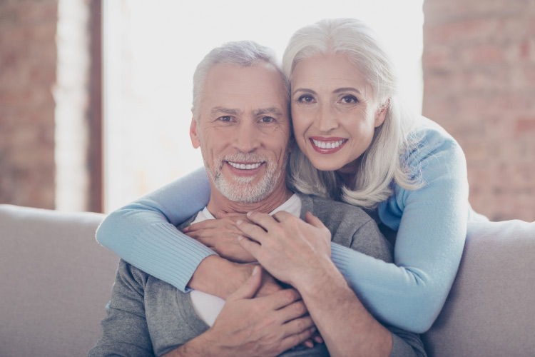 Older white-haired couple with dental implants embrace while sitting on a couch