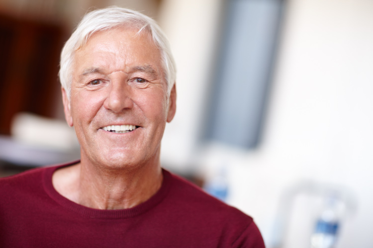 White-haired man with dentures smiles while wearing a red shirt