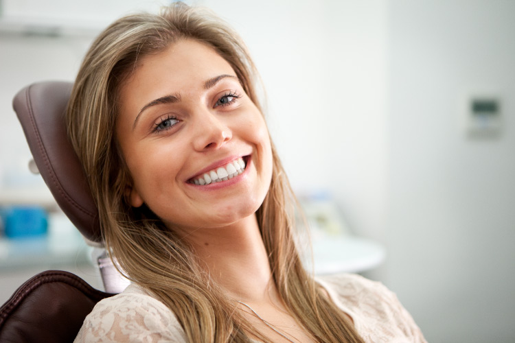 Brunette woman smiles while sitting in a dental chair about to receive root canal therapy to preserve her natural tooth