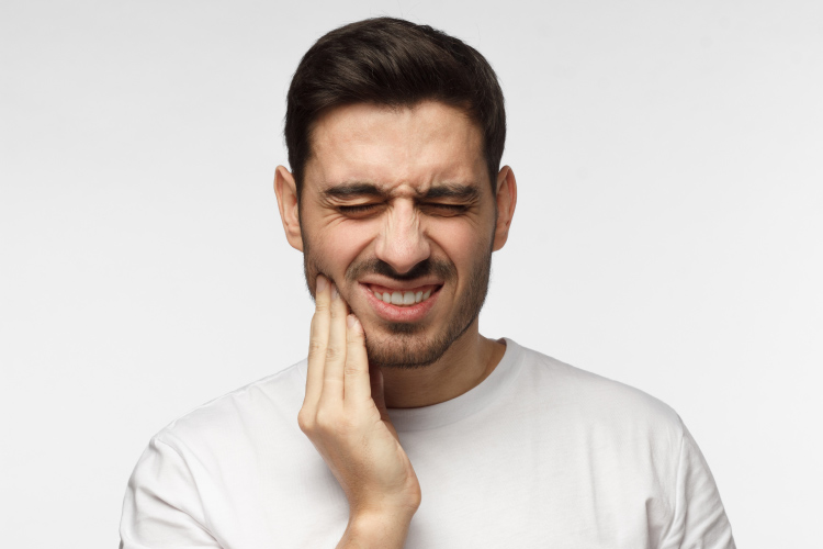 Dark-haired man cringes in pain and touches his cheek due to a toothache dental emergency