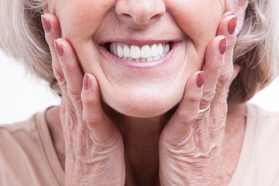 Close up of a mature woman with her hands on her cheeks showing off her new porcelain veneer smile