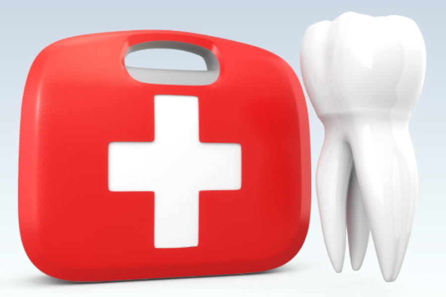Red emergency kit with a white cross next to a model of a tooth.