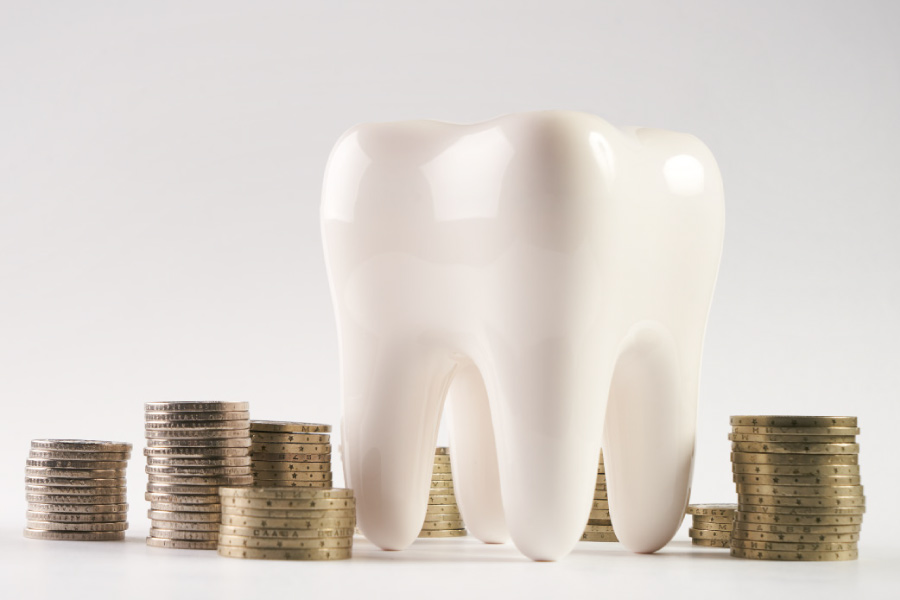 Model of a tooth next to stacks of coins.